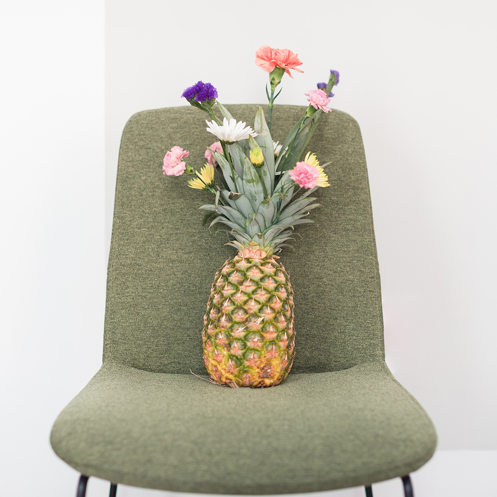 pineapple with flowers sitting on chair