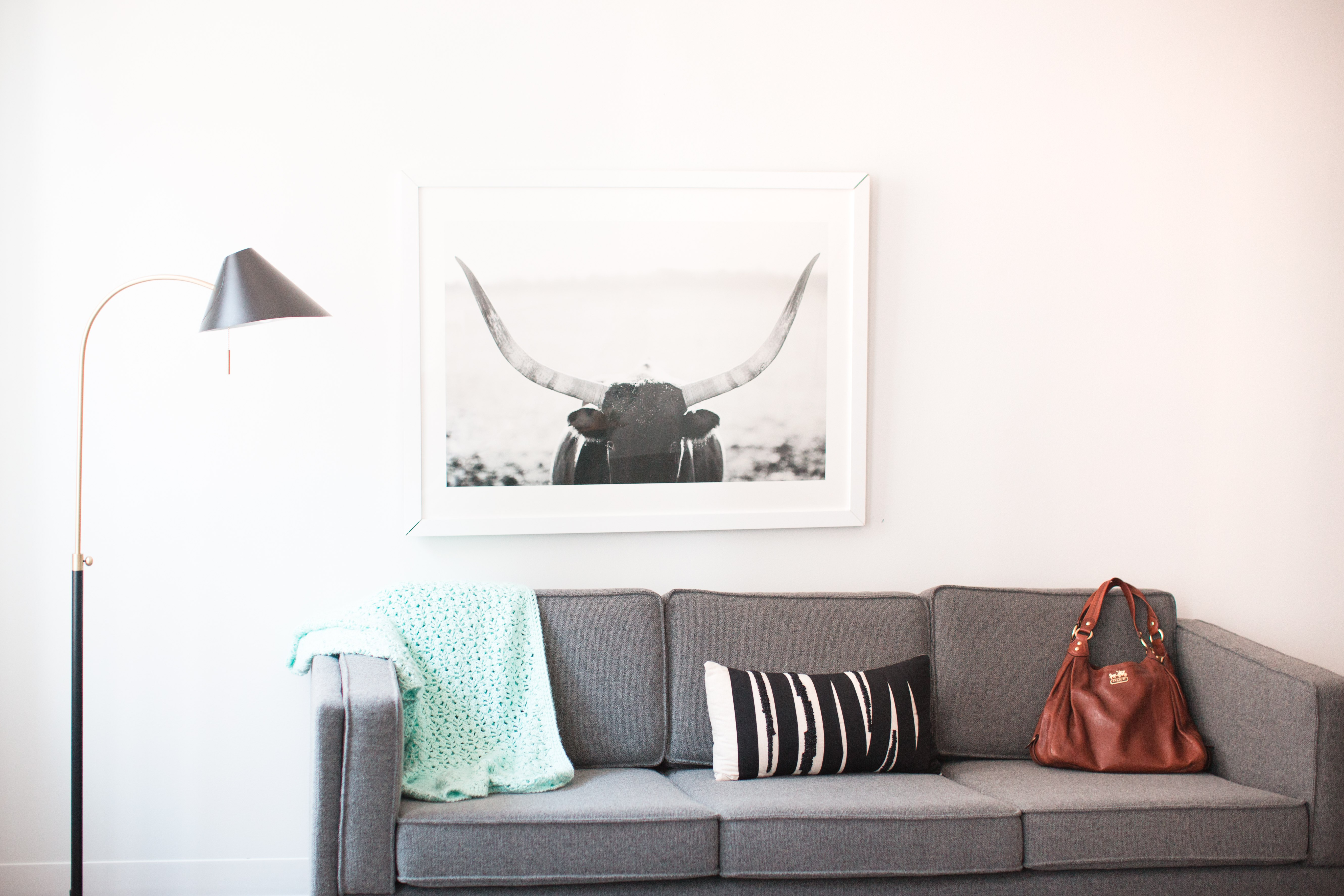 Grey couch with a picture of a cow above it