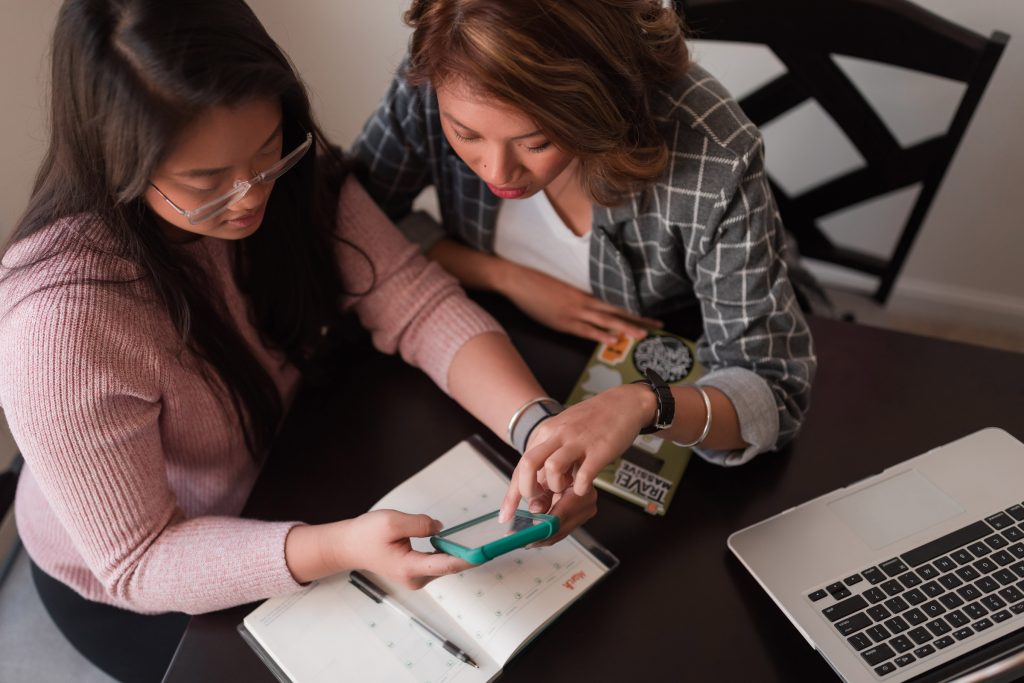 Two women sitting at a desk looking at a phone together