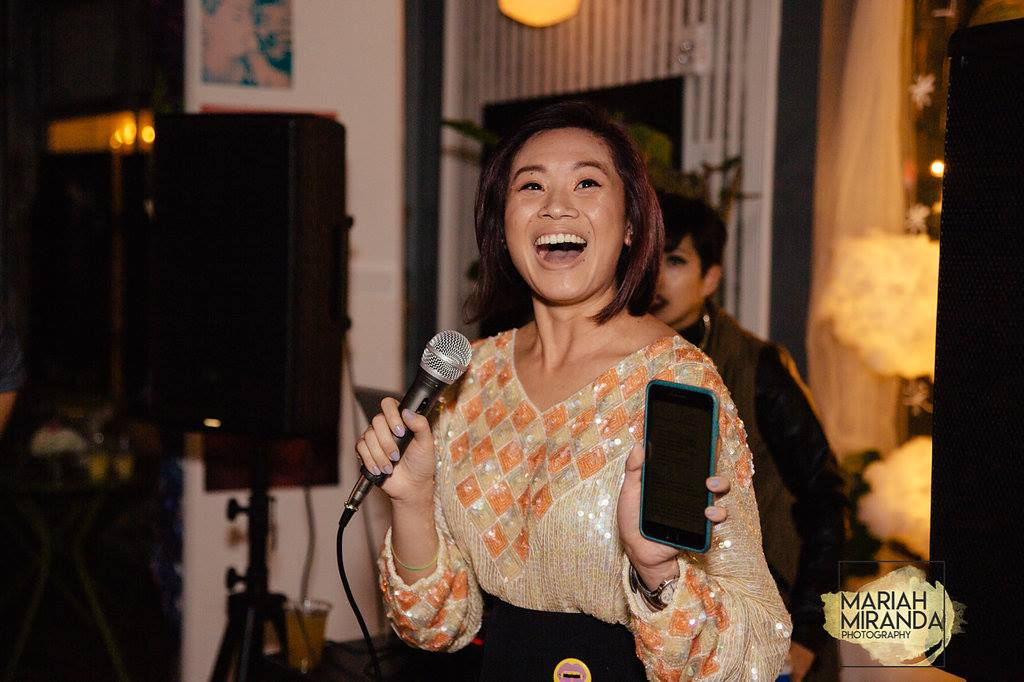 Cassandra of The Quirky Pineapple Studio hosting an event holding a microphone and cell phone