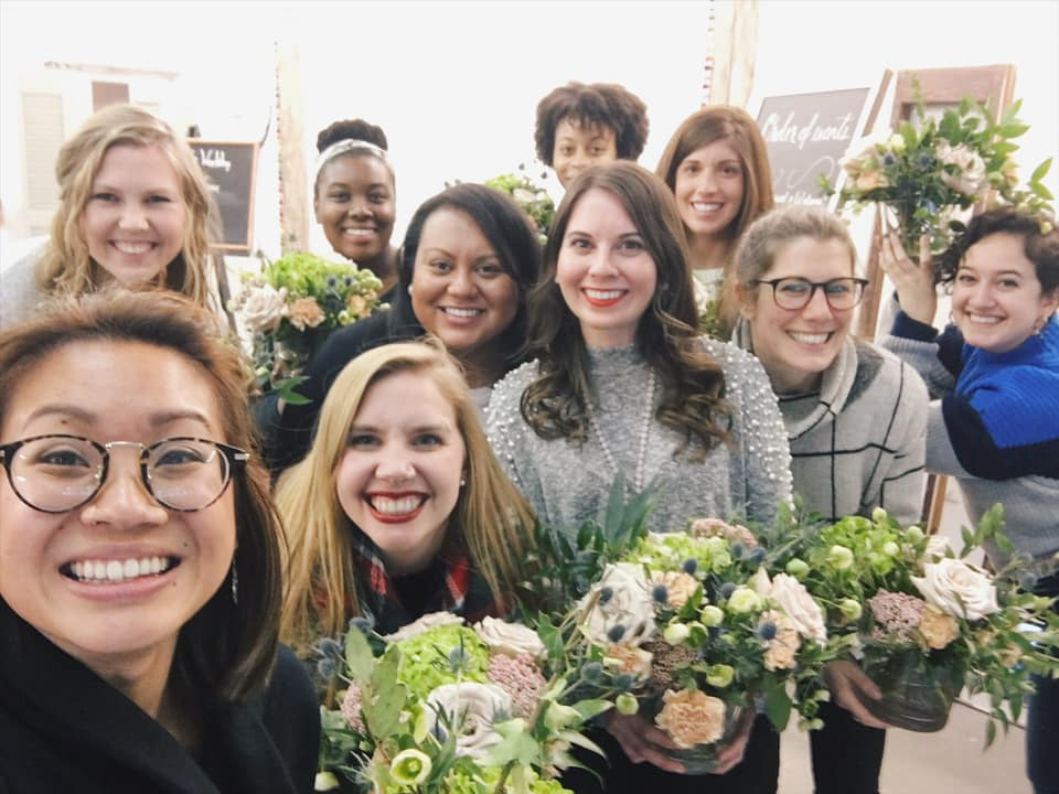 Group of female creative business owners holding floral arrangements at a Creative's Workday event hosted by The Quirky Pineapple Studio