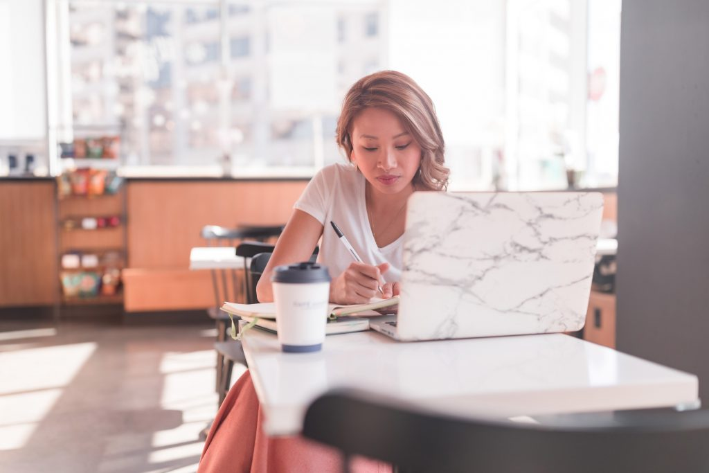 Copywriter sitting in coffee shop to reset her mind for business growth