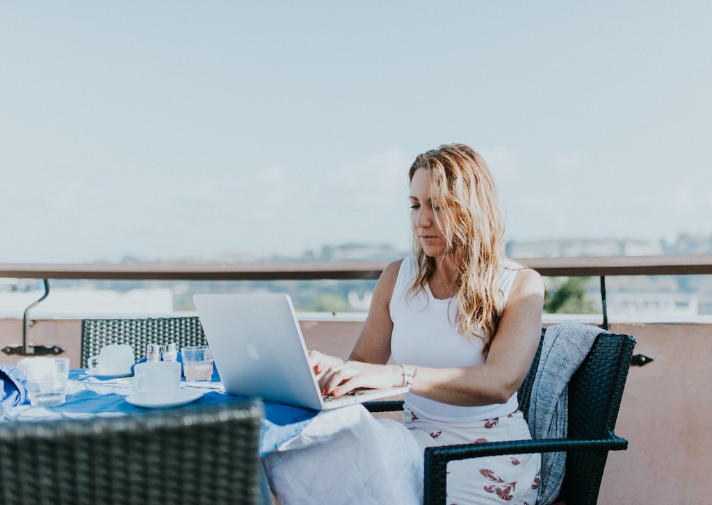 womxn working from her laptop outside with cloudy skies behind her