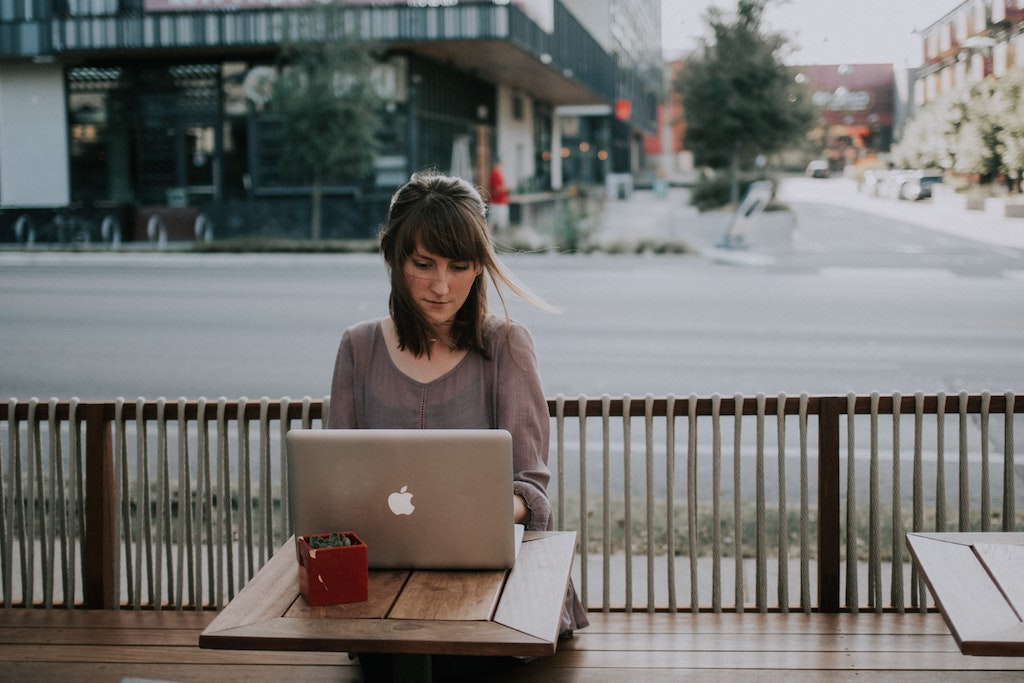 womxn sitting outside with her laptop working on her brand messaging framework